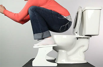 Clothed woman squats over a toilet using Squatty Potty